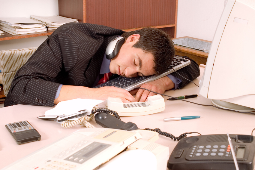 Businessman sleeping in his office at table with computer