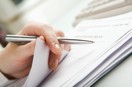 Close-up of hand holding pen with paper over pile of documents