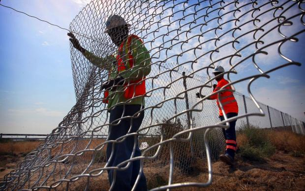 Caltrans highway maintenance workers, Don Causey, left, and Jason Bruins repair a fence along Interstate 15 in Eastvale in the blistering heat on Tuesday, June 21, 2016. Outdoor workers are suffering the most in this record-breaking June heatwave.