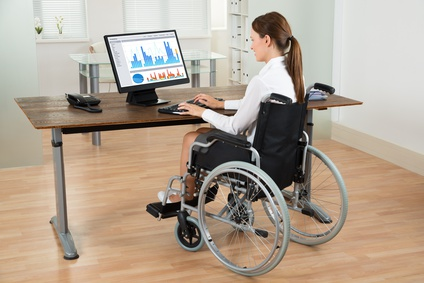 Young Businesswoman On Wheelchair Analyzing Graph On Computer In Office