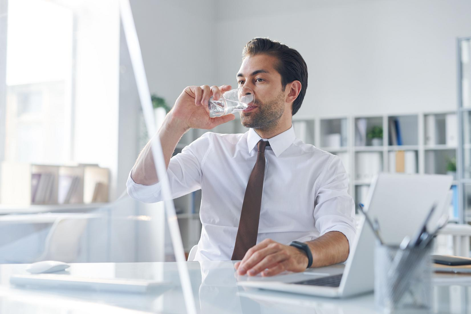 Thirsty young broker having glass of water